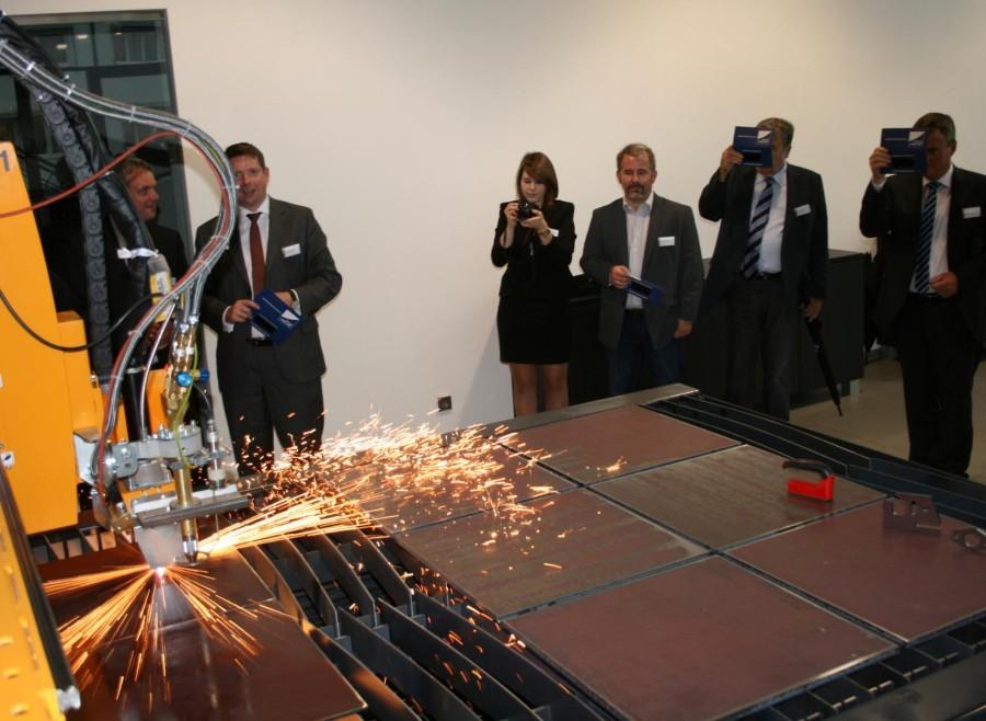 Die Festgäste aus Politik und Wirtschaft erlebten im Kompetenzzentrum von Microstep, wie eine Plasmaschneideanlage mit rund 30000 Grad Hitze aus dicken Stahlplatten filigrane Werkstücke herausschneidet.